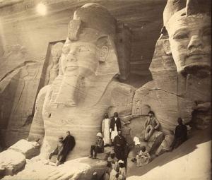 Crno-bela fotografija hrama zatrpanog peskom i grupe ljudi pored njega