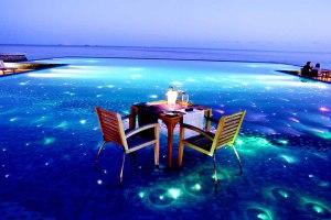 Romantično postavljen sto za večeru sa svećama, koji je odmah pokraj prelepe bistre vode