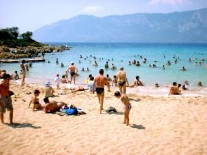 Slika plaže, mora i ljudi kako se kupaju